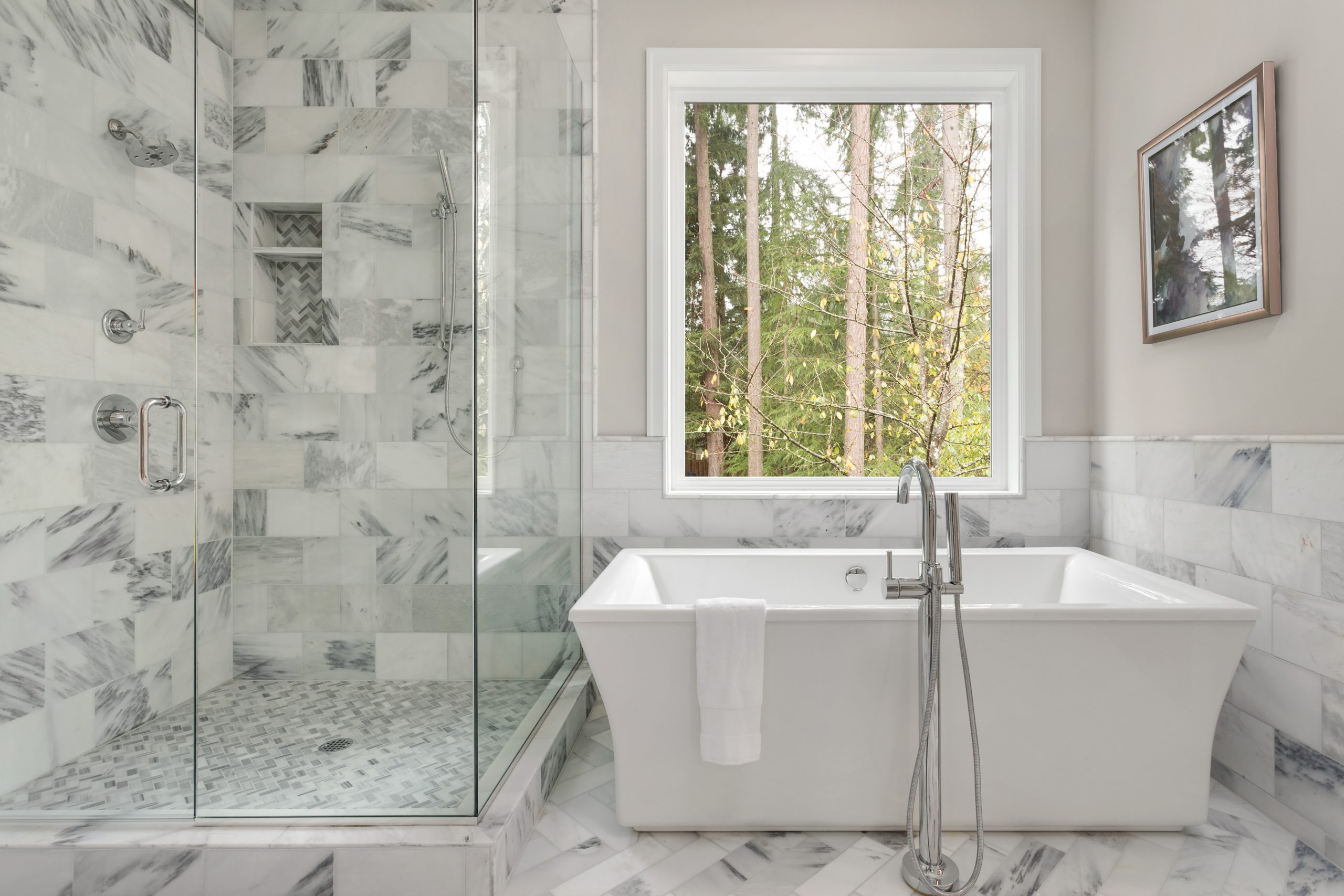 Bathroom with bathtub and shower in new luxury home with all glass shower. Large window allows for abundant natural light.
